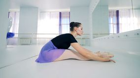 Lady dancer is stretching in a sitting position if front of a mirror stock footage