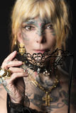 Lady in dark , with tattoo onface with mask Stock Image