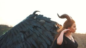 Lady dark vintage dress with huge heavy strong wings behind her back removes her long hair from her face with gentle