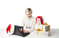 Lady at desk with present boxes and hat over white Stock Photos