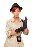 Lady Detective Puts on Her Gloves In Trench Coat on White. Attractive Female Detective With Badge and Leather Gloves In Trench Coat Isolated on a White Royalty Free Stock Image
