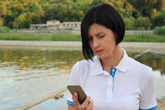 Lady dials the number on smartphone. Young woman portrait in summer. girl is reading message on cell phone outside in park near the lake.. Female in a white Stock Photo
