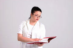 Lady Doctor in Clinicall Clothes is Reading Diagnose Book. Lady Doctor in Clinical Clothes is Holding Diagnosis Book Royalty Free Stock Image