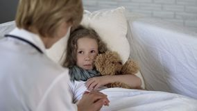 Lady doctor comforting scared little child before examination, medical services stock images