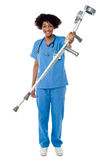 Lady doctor handing over crutches to the patient Stock Images