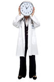 Lady doctor holding clock before her face Stock Images