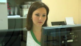 A Lady-Doctor launches an MRI scanner and looking on resultates on monitor. stock footage