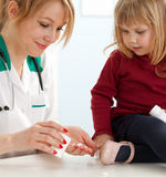 Lady doctor with little girl in exam room Royalty Free Stock Photos