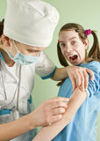 Lady doctor making an injection. To scared teen girl Stock Photography