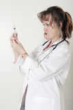 Lady doctor prepping up a syringe Stock Photos