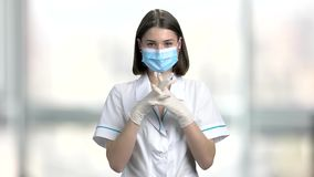 Lady doctor putting on protective gloves. Beautiful female doctor in face mask preparing for operation. People, medicine, healthcare stock video