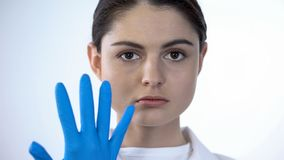 Lady doctor putting on surgical gloves, preparing to examine patient, medicine stock images