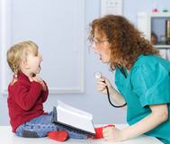 Lady doctor with stethoscope exam baby mouth Royalty Free Stock Images
