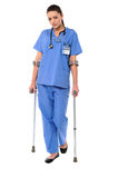 Lady doctor walking with help of crutches Royalty Free Stock Photography