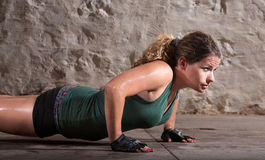 Lady Does Push-ups. One beautiful young woman doing push ups indoors Royalty Free Stock Images