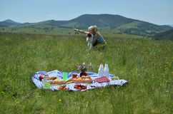 Lady and Dog on Picnic Day. Lush picnic with lady showing something in distance to her dog and with hills in background Stock Images