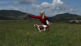 Lady and Doggy. Lady playing with her dog (Cavalier King Charles Spaniel) in a mountain meadow with hilly landscape behind stock footage