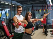 A lady doing exercises with red dumbbells on a gym background. A personal trainer helping a client on a fitness club. stock image