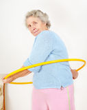 Lady doing gymnastic with hula-hoop. Portrait senior lady doing gymnastic with hula-hoop Royalty Free Stock Photography
