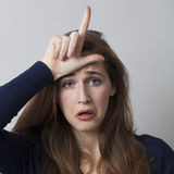 Lady doing the loser sign on her forehead. Sad young woman making the L sign on forehead for loser message, cool hand gesture for youth culture royalty free stock photography