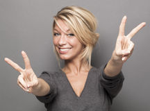 Lady doing the peace sign. Satisfaction concept - sign of double victory in the foreground for excited young woman with trendy blonde hair Royalty Free Stock Image