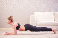 Lady doing plank exercise. Abdominal strength. Pretty young lady doing plank exercise at home in white decorated room stock photography