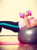 Lady is doing some workout. Sport, gym, people concept. Lady is doing some workout. Woman has dumbbell in her hands and she lying on the fit ball Royalty Free Stock Photo