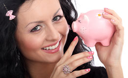 Lady doll with pig money-box. Beautiful lady holding a pig money-box stock photography