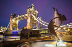 The lady and the dolphin fountain with Tower Bridge at night, London, UK Stock Photo