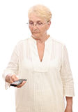 Lady in doubt with remote control Royalty Free Stock Photography