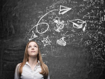 A lady is dreaming about graduation. Math formulas, an arrow, geometric figures are drawn on the black chalkboard. Stock Photography