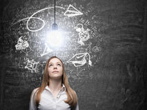 A lady is dreaming about graduation. Math formulas, an arrow and geometric figures are drawn on the black chalkboard. A Stock Photo