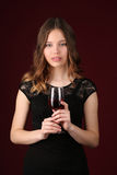 Lady in dress holding glass of wine. Close up. Dark red background Stock Photography