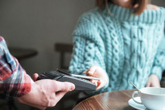 Lady dressed in sweater pays for her order with phone Stock Photo