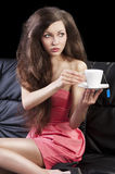 Lady drinkig tea, she take a cup of tea. Sophisticated young pretty brunette in pink elegant dress sitting on a black sofa and tasting a cup of tea. she looks at Stock Photography