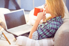 Lady drinking coffee in front of laptop Royalty Free Stock Photography