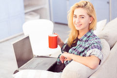 Lady drinking coffee in front of laptop Stock Images