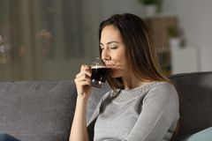 Lady drinking coffee at home in the night. Lady drinking coffee in the night sitting on a couch in the living room at home Royalty Free Stock Image