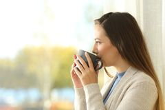 Lady drinking coffee and looking through a window. Side view portrait of a relaxed lady drinking coffee and looking outdoors through a window at home Royalty Free Stock Photography