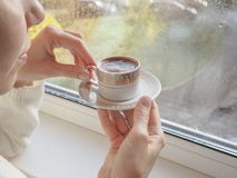 Lady drinking coffee by the window. Royalty Free Stock Images