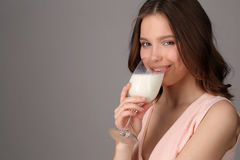 Lady drinking milk from a bocal. Close up. Gray background Royalty Free Stock Photo