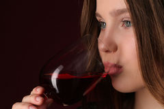 Lady drinking wine. Close up. Dark red background. Lady drinking wine, girl with wineglass, high fashion look, beautiful girl, brunette girl, isolated, model in Royalty Free Stock Image