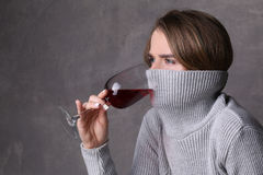 Lady drinking wine with collar on her face. Close up. Gray background Royalty Free Stock Image