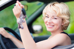 Lady, driving showing car keys out the window. Woman, driving showing car keys out the window. Young female driving happy about her new car or drivers license Royalty Free Stock Image