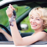 Lady, driving showing car keys out the window. Woman, driving showing car keys out the window. Young female driving happy about her new car or drivers license Stock Photography