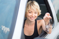Lady, driving showing car keys out the window. Royalty Free Stock Image