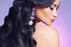 Lady with earring. Fashion studio portrait of beautiful young woman with earring. Jewelry and accessories Stock Photos