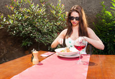 Lady eating lunch and wine outside on terrace Stock Photo