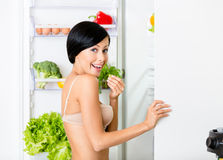 Lady eating near the opened fridge Royalty Free Stock Photos