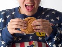 Lady eats hamburger. Ladi in american flag style sweater eats hamburger stock photos